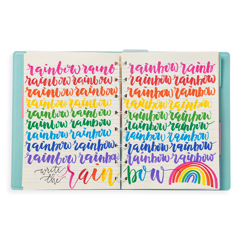 Image of planner open with rainbow written in brush lettering in rainbow colors