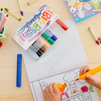 Image of a kid's hands coloring a coloring book on a table with Big Bright Brush Markers