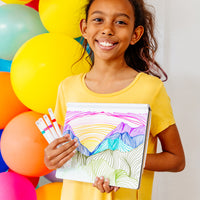Girl holding her pack of Drawing Duet Double Ended Markers smiling