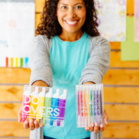 Happy teacher holding up radiant writers and do-overs highlighters