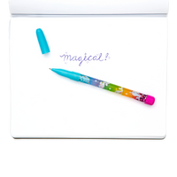 Blue Rainbow Glitter Wand Ballpoint Pen shown with writing in notebook