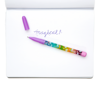 Purple Rainbow Glitter Wand Ballpoint Pen shown with writing in notebook