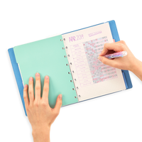 Image of a person writing with an OOLY Color Click Mini 6 in 1 Ballpoint Pen in a Journal