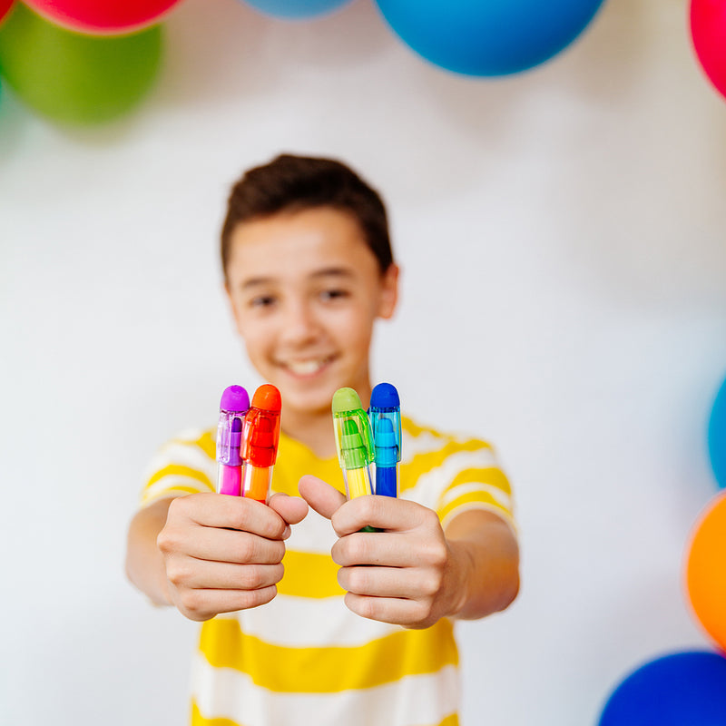 Smiling boy holding Presto Chango Jumbo Crayons in both hands