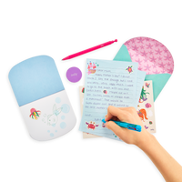 Hand writing with 21 pieces of stationery in the Magical Mermaids On-The-Go Stationery Kit. Letter sheets, envelopes, a notebook, mechanical pencil and more