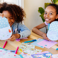 Two girls holding their letters to grandma using the On-The-Go Travel Stationery Kit - Funtastic Friends