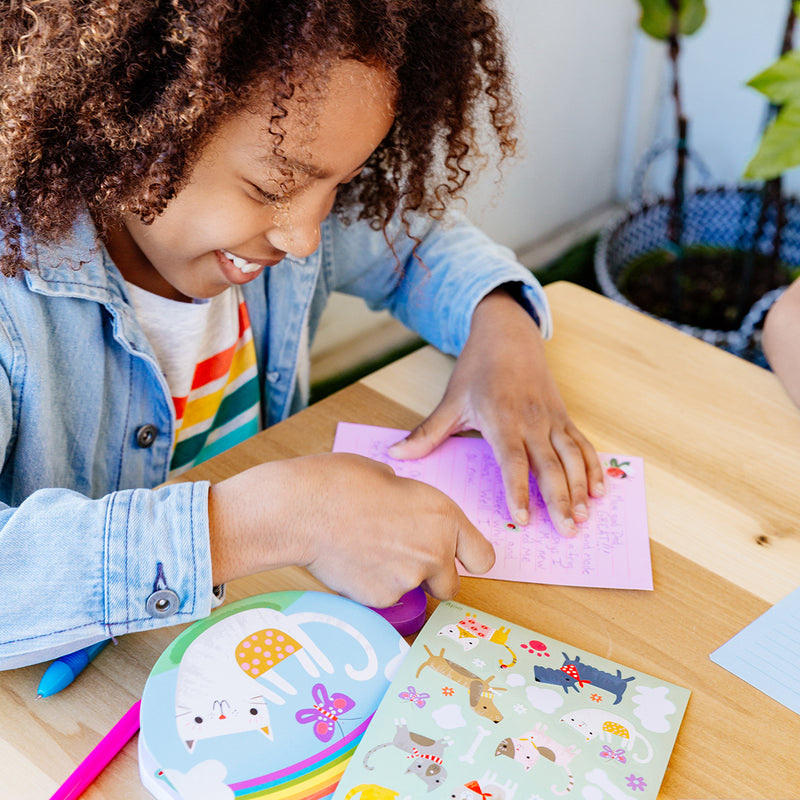 Image of a young girl having fun decorating her letter from the On-The-Go Travel Stationery Kit - Paw Pals