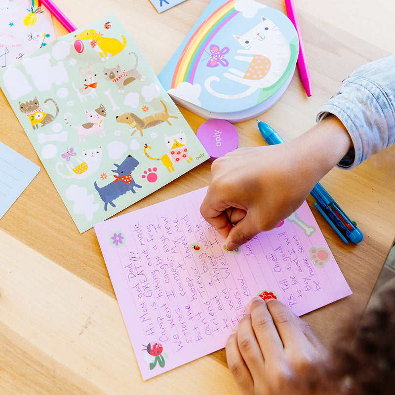 Image of a girl writing a letter with her OOLY On-The-Go Travel Stationery Kit