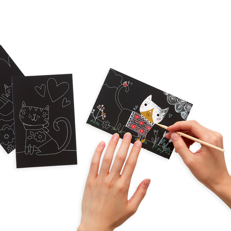 Lifestyle image of person using the Cutie Cats Scratch and Scribble Mini Scratch Art Kit