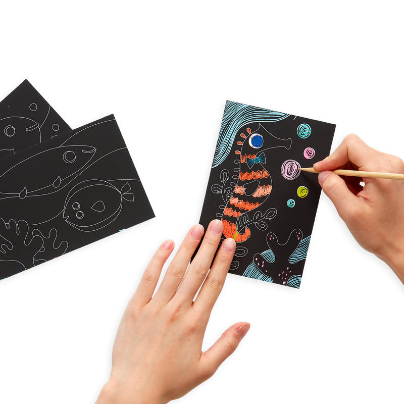hands drawing on Friendly Fish Scratch and Scribble Mini Scratch Art Kit