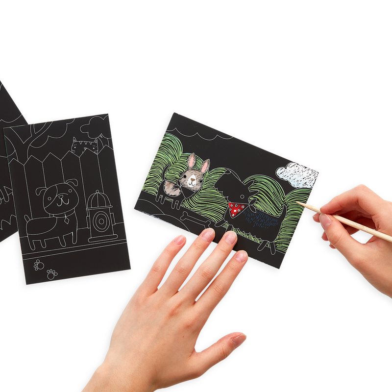 Hands scratching the Playful Pups Scratch and Scribble Mini Scratch Art Kit with the included wooden stylus