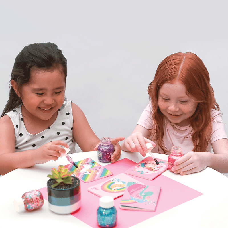 Two girls painting unicorn notebooks with Pixie Paste brush-on glitter glue