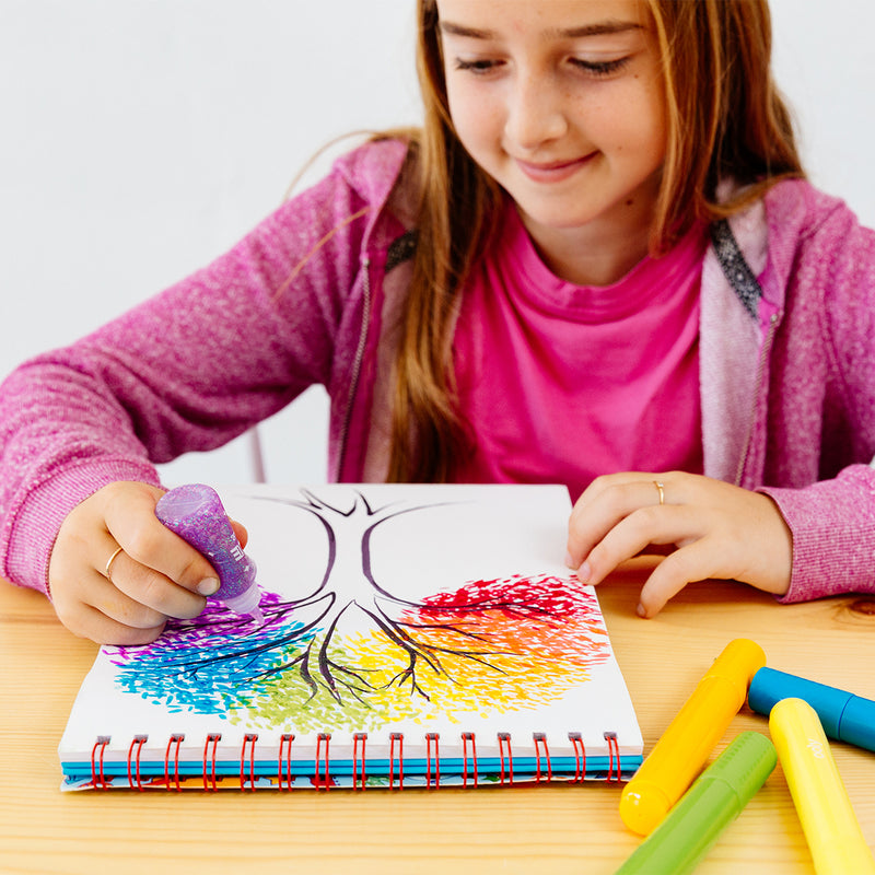Girl working on colorful tree art with purple rainbow sparkle glitter glue