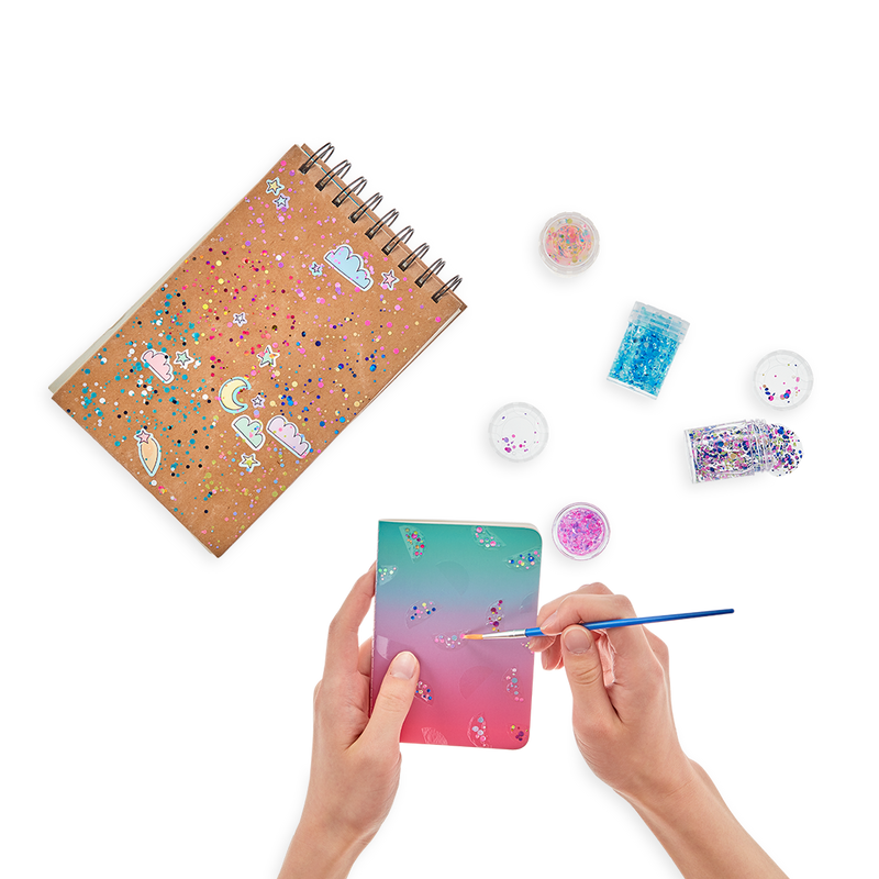 Display of person using the OOLY Mini Dots Pixie Paste Glitter Glue on a journal