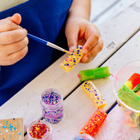 Child painting a pasta with the OOLY Mini Dots Pixie Paste Glitter Glue