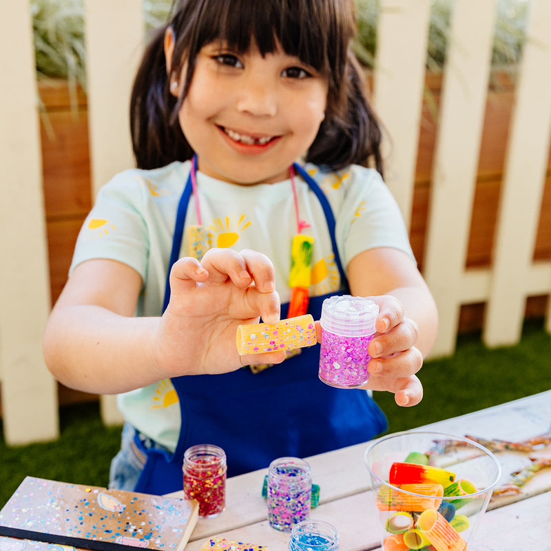 Girl holding her pasta project and Mini Dots Pixie Paste Glitter Glue