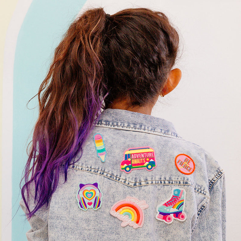Girl wearing denim jacket with OOLY iron on patches