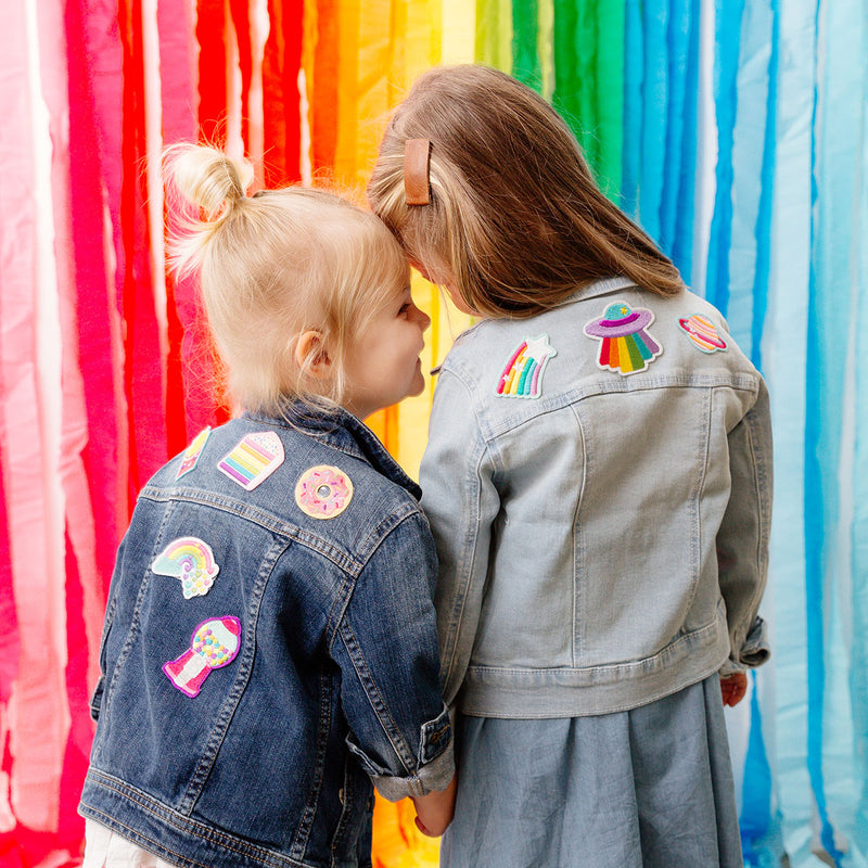 Two girls holding hands with denim jackets with OOLY patches with a rainbow background