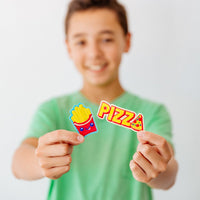 Smiling boy in green shirt holding up fries and pizza patches