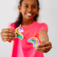 Smiling girl in pink shirt holding up unicorn and rainbow patches
