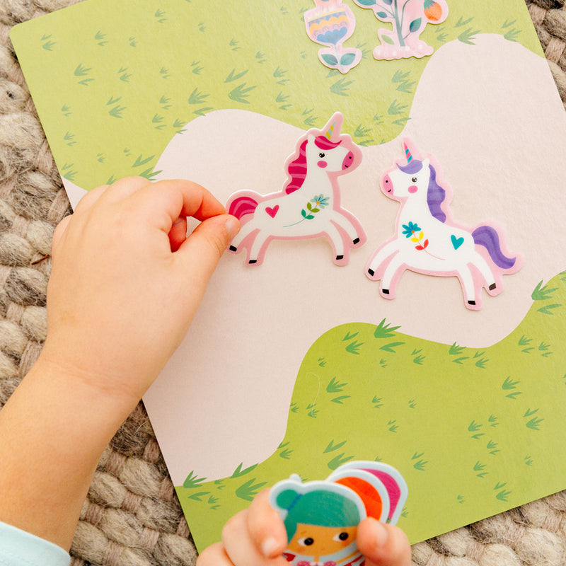 close-up of childs' hands playing with stickers from Play Again! Reusable Sticker Scenes - Princess Garden