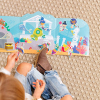 Child sitting on floor playing with Play Again! Reusable Sticker Scenes - Mermaid Magic