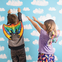 Boy and girl playing with 3D Colorables dress up wings; dragon and butterfly wings