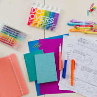 Teacher's desk with blue Oh My Glitter notebooks and other colorful OOLY products