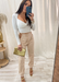 Women's white long sleeve sweetheart top with our 3 side gold chains beige joggers and gold Audrey clear heels and gold clutch.