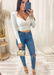 Women's white long sleeve sweetheart top with jeans and nude clear heels, Audrey heels by Alexandria Brandao, with Coach snake print small handles purse.