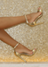 Ali heels in Gold against a light gold background. Side view