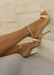 Ali heels in gold propped against a titled wall. Side view