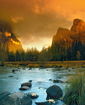 The Peaks at Yosemite National Park at dusk with the Merced River in the foreground.