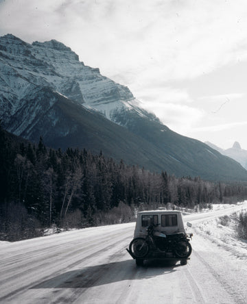 Peter Lik driving his vintage white van with motorcycle on rear bumper driving through the snow covered roads in Alaska.