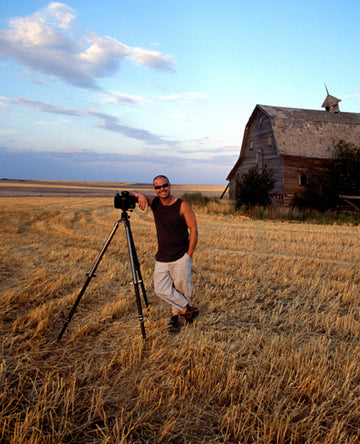 Portrait of Peter Lik standing in front of barn with his tripod in a grassy field.