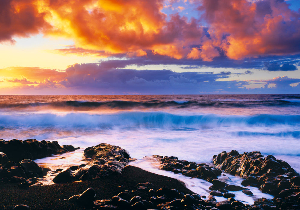 Waves crashing onto a rocky beach in Hana Hawaii with the sun rising into a cloud filled sky
