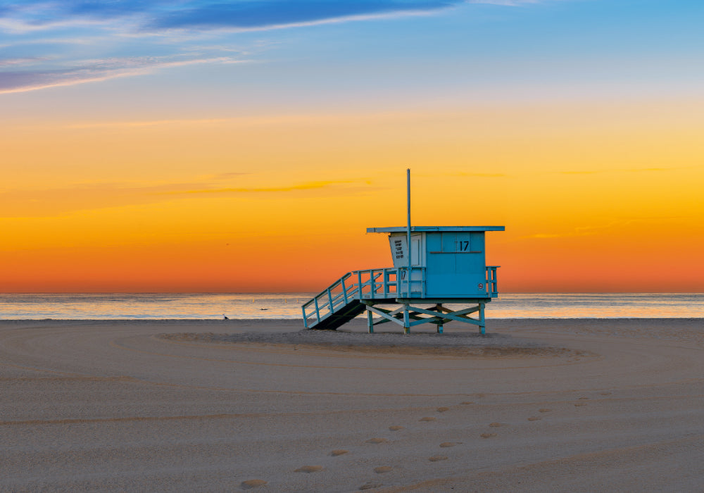 Blue life guard shack on the sandy beach of Santa Monica California at sunset