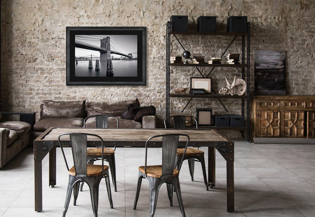 New York loft with aged brick walls, industrial furniture and a framed black and white photograph of Manhattan Bridge