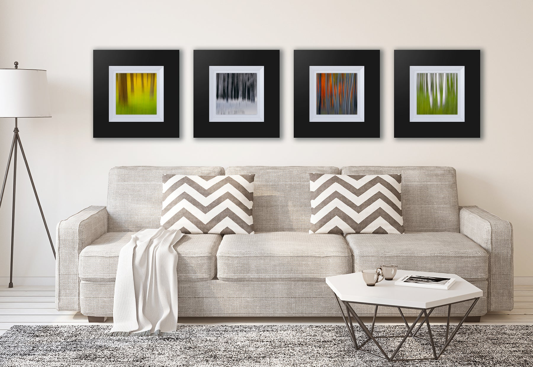 Living room with gray couch and white table featuring four framed square photographs of blurred Aspen trees by Peter Lik in dark brown frames with white linen liners