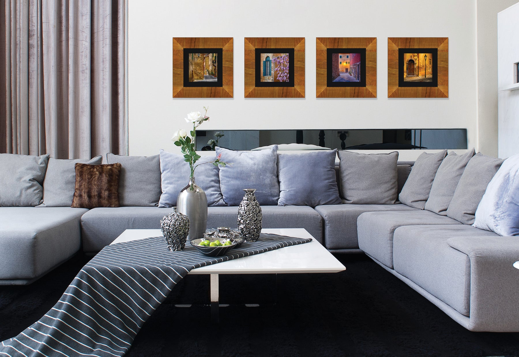 Modern living room with gray couch and white table featuring four framed square photographs of Italy by Peter Lik in light brown frames with black linen liners