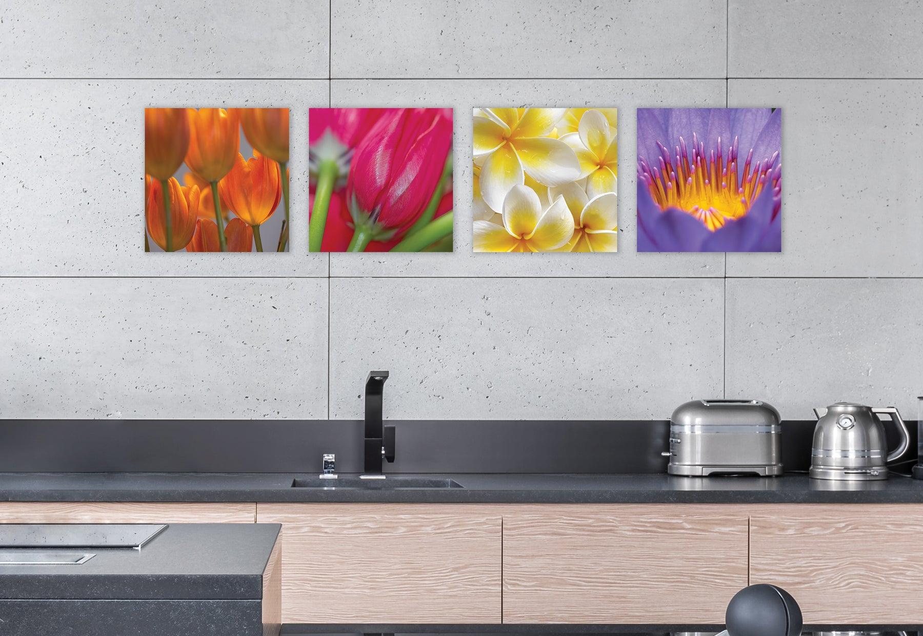 Sleek modern kitchen with light brown cabinets, dark gray countertops and concrete walls featuring four square photographs of colorful flowers by Peter Lik