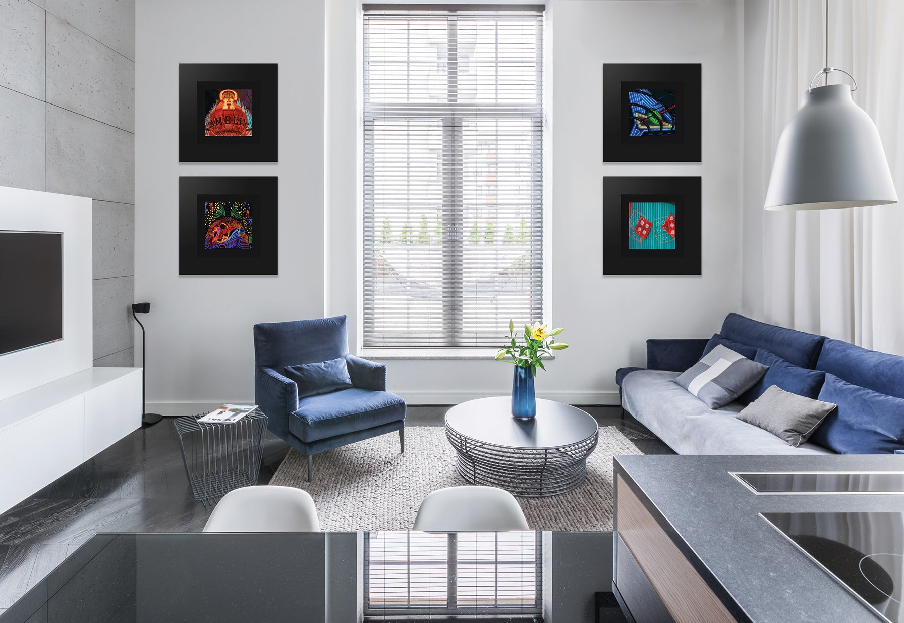 Modern home interior with blue couch and chair featuring four square photographs of Las Vegas landmarks by Peter Lik in matte black frames and black liners
