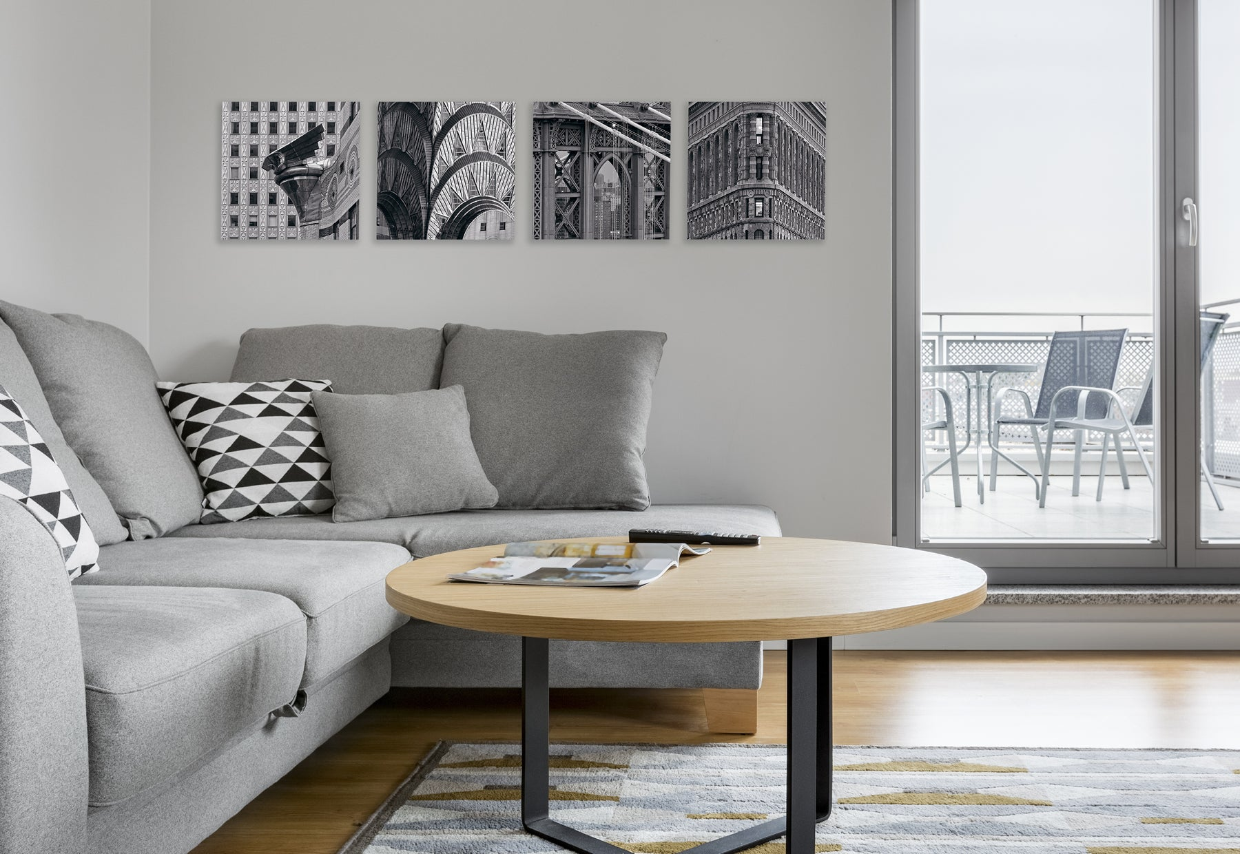 Living room with light gray couch and light brown coffee table featuring four square black and white photographs of iconic New York City landmarks by Peter Lik