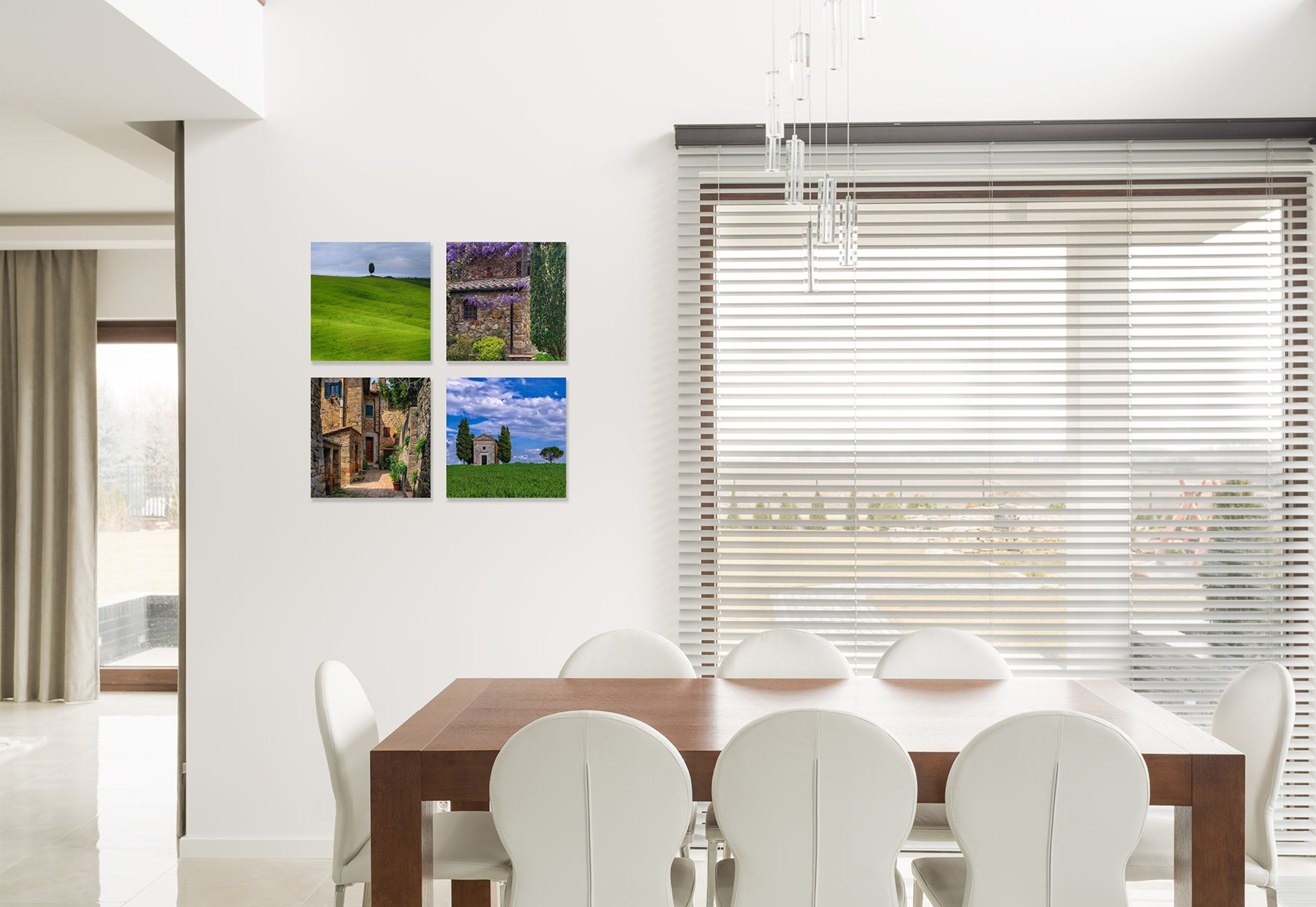 Residential dining room with brown table and white chairs featuring four framed photographs of France by Peter Lik