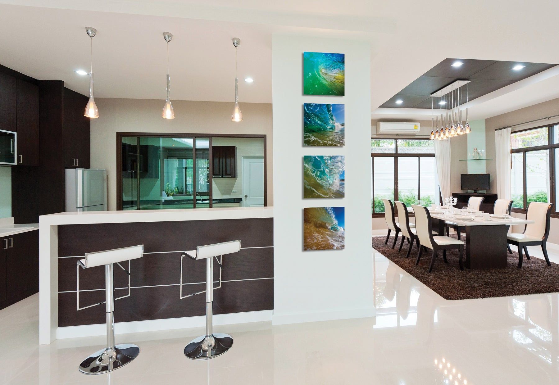Modern kitchen and dining interior featuring four square photographs of ocean waves by Peter Lik hanging next to bartop