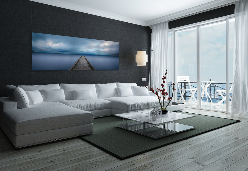 Living room with dark gray wall and white couch featuring a photograph of a pier reaching out into cloudy skies and blue water