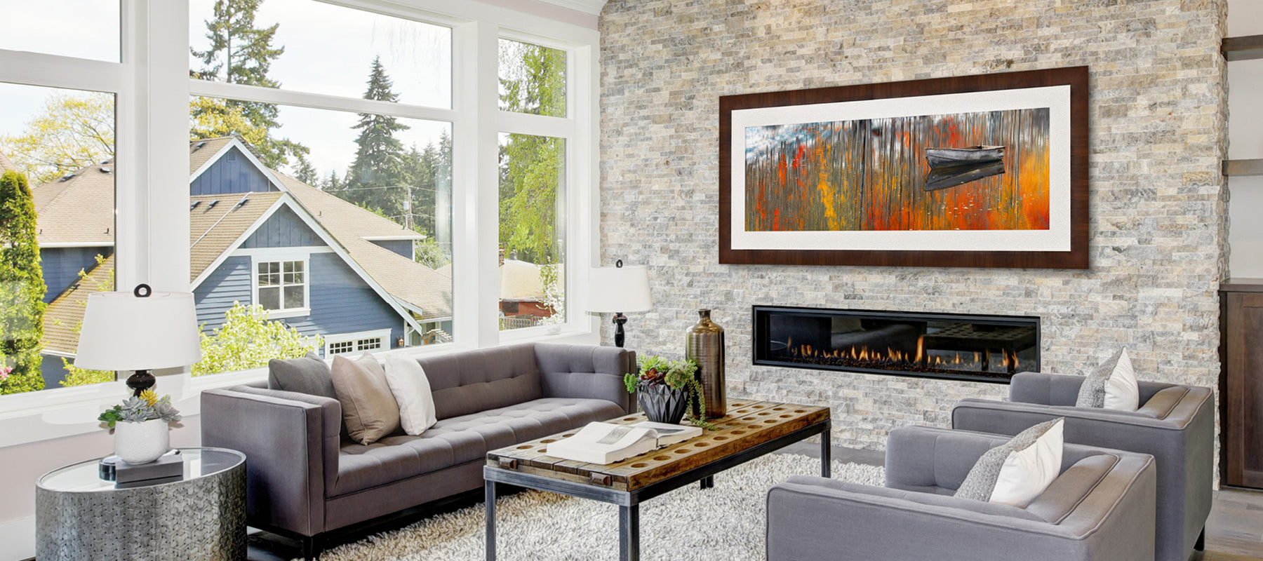 Modern living room with light gray fireplace featuring a framed photograph by Peter Lik of a rowboat on a lake in Aspen