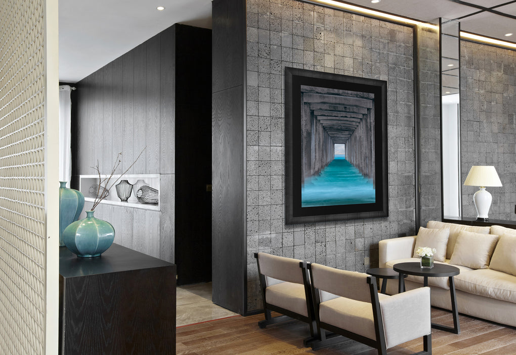 Office lobby with white chairs and a gray stone featuring a photograph of Scripps Pier from below in Pacific blue water