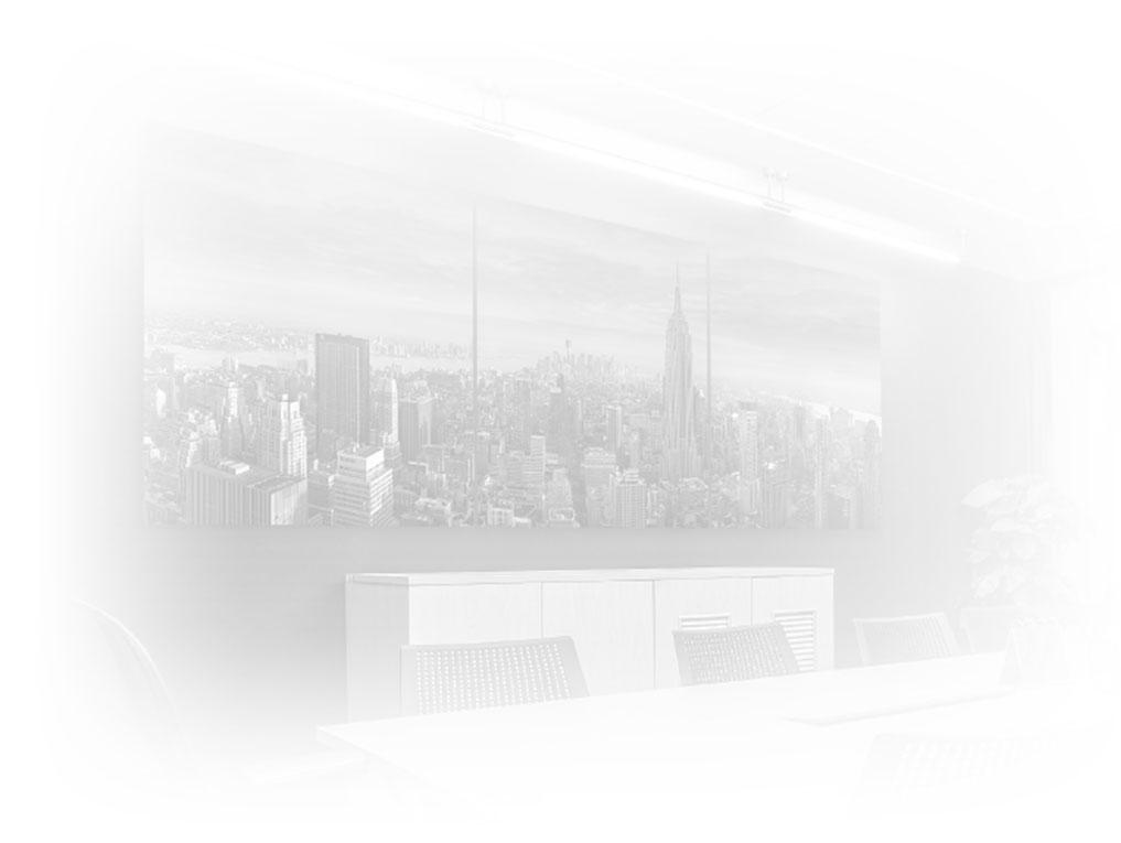 Light gray background of a corporate conference table with a framed 3-panel photograph of Manhattan, New York with Empire State Building