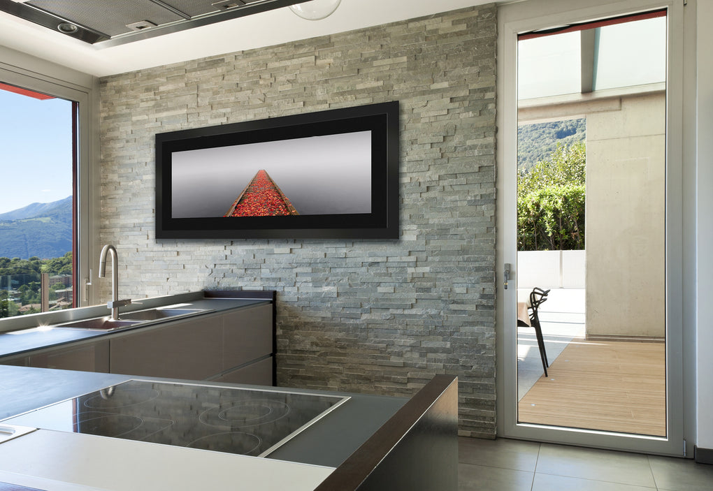 Modern kitchen with gray stone wall featuring a framed photograph of a pier covered in orange leaves during a misty morning